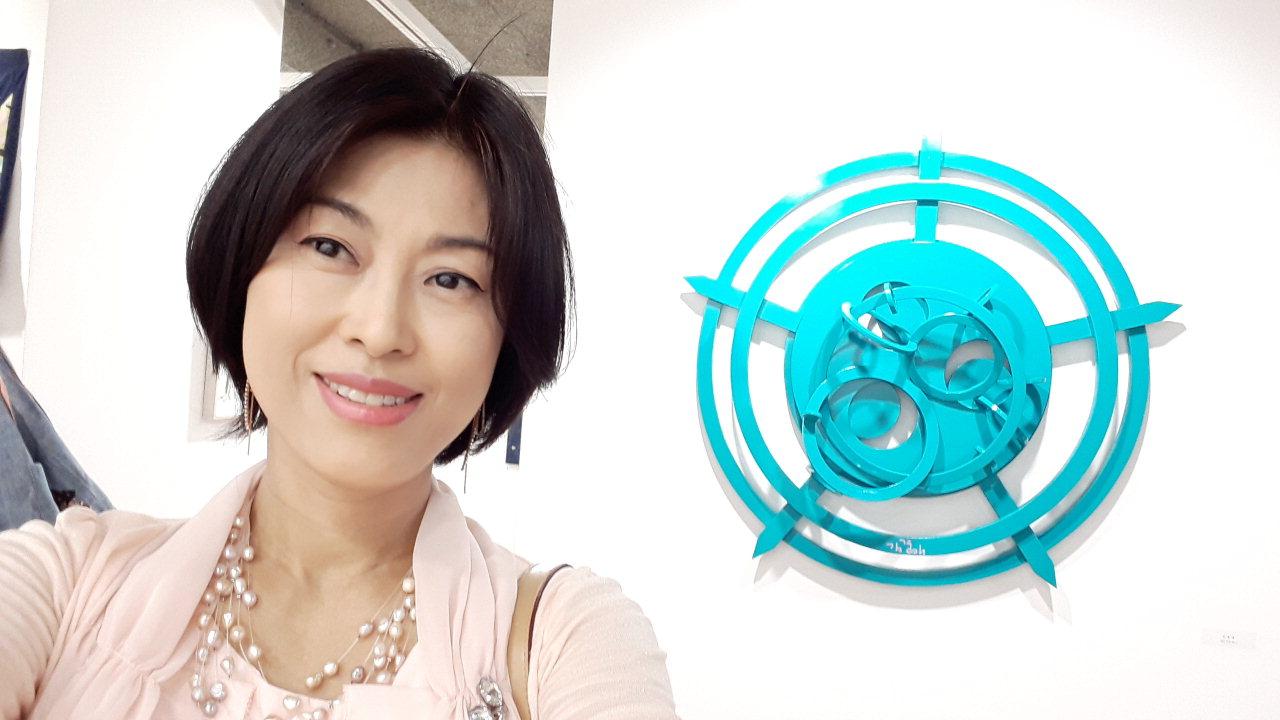 김경애 작가가 자신의 작품 앞에서 포즈를 취하고 있다.